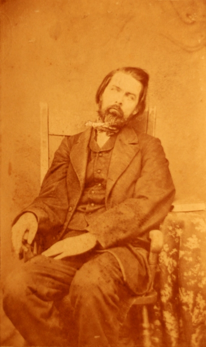c1860 post-mortem photograph of a deceased man. The body is arranged so as to appear lifelike.[Source: Public Domain]