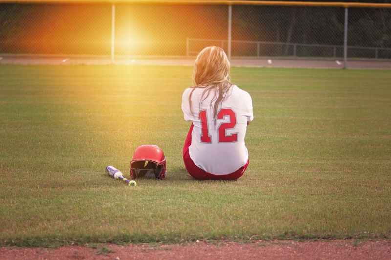 female baseball player sitting on grass field beside helmet and baseball bat